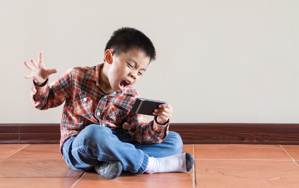 Young boy frustrated with smartphone