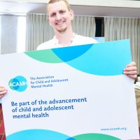 Dr Max Davie, Paediatrician, holding a sign about ACAMH