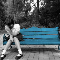 Sad student in school uniform is crying sad alone on the bench in the park after school.